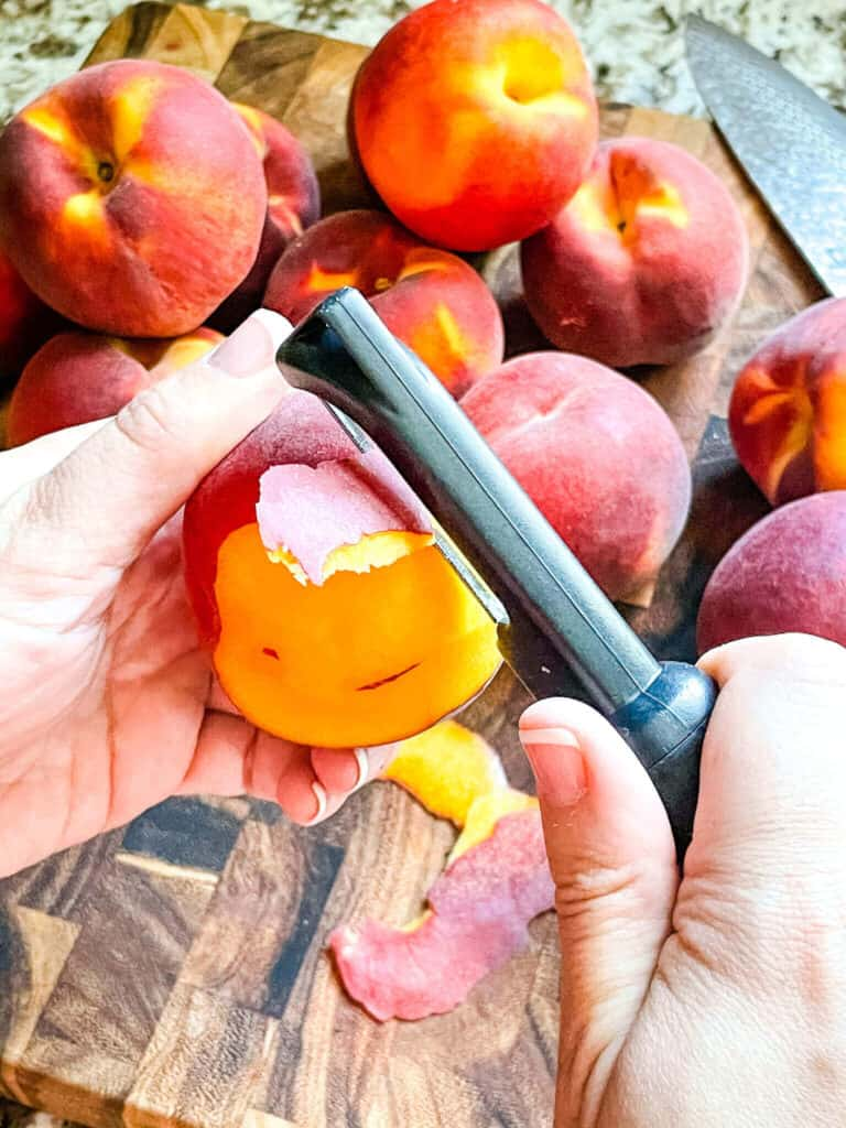 A hand using a peeler on the fruit