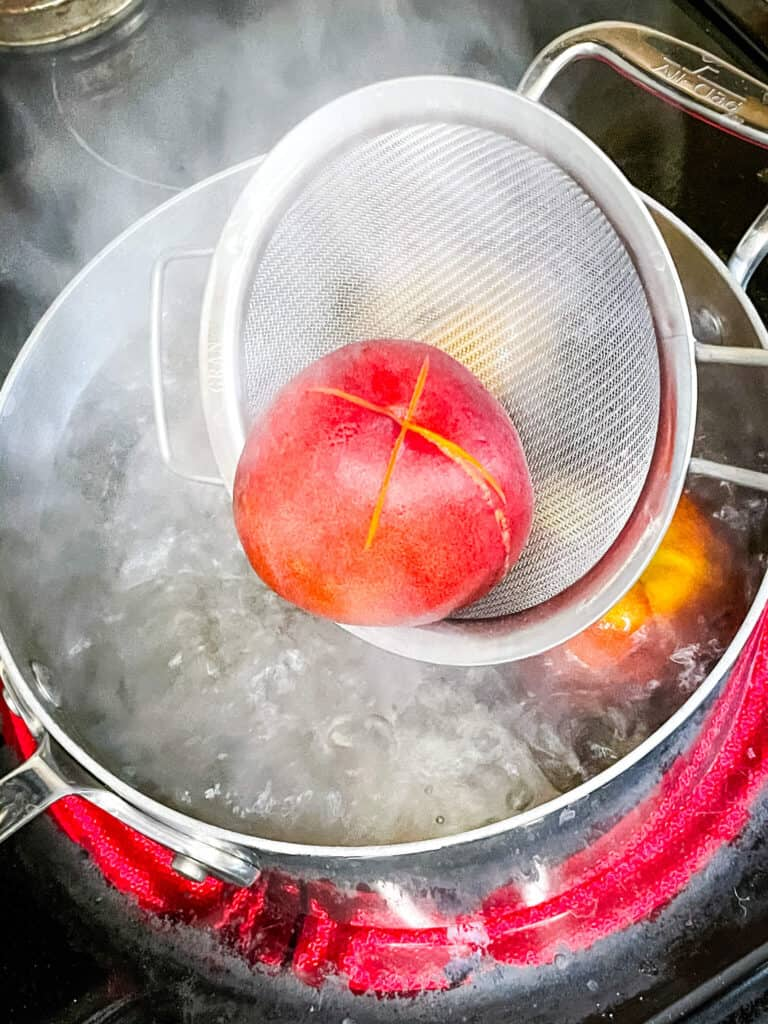 A strainer scooping a peach from boiling water