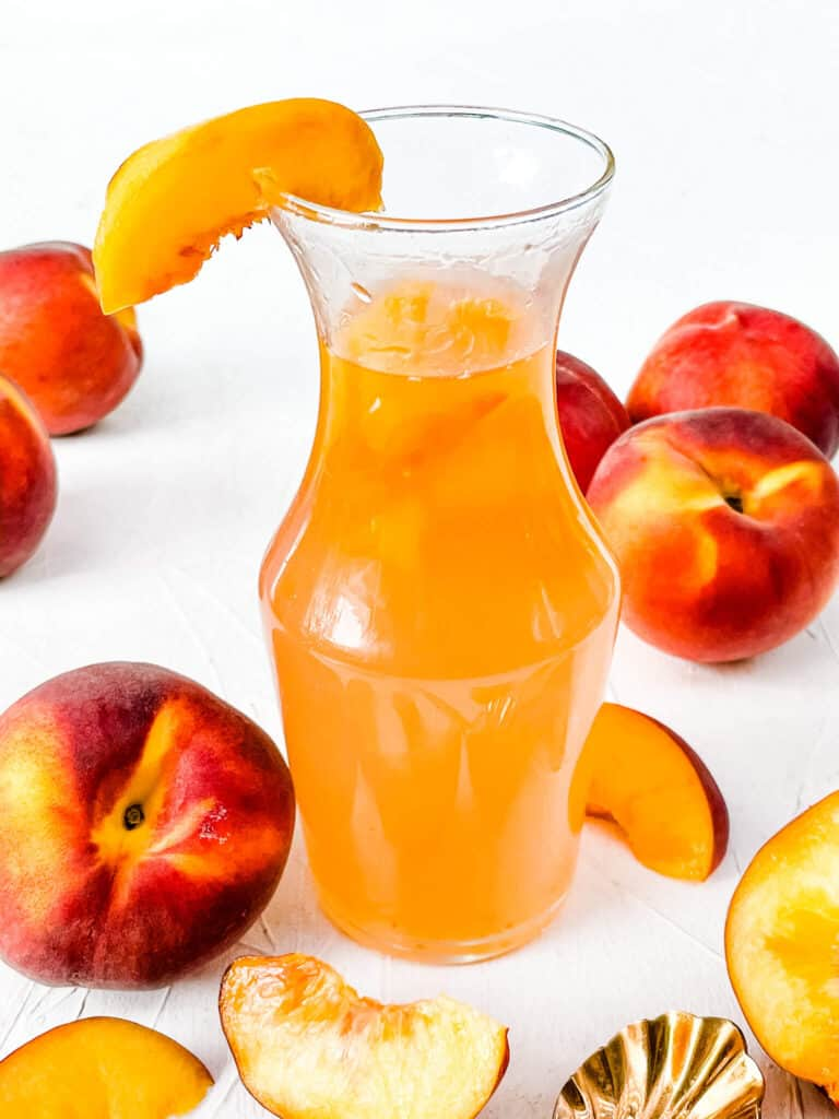 A jar full of Peach Syrup with peaches around it