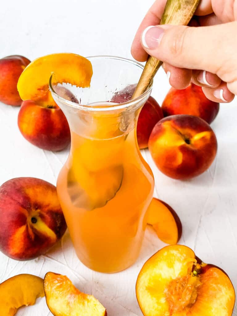 A hand dunking a spoon into a jar of Peach Syrup with peaches around it