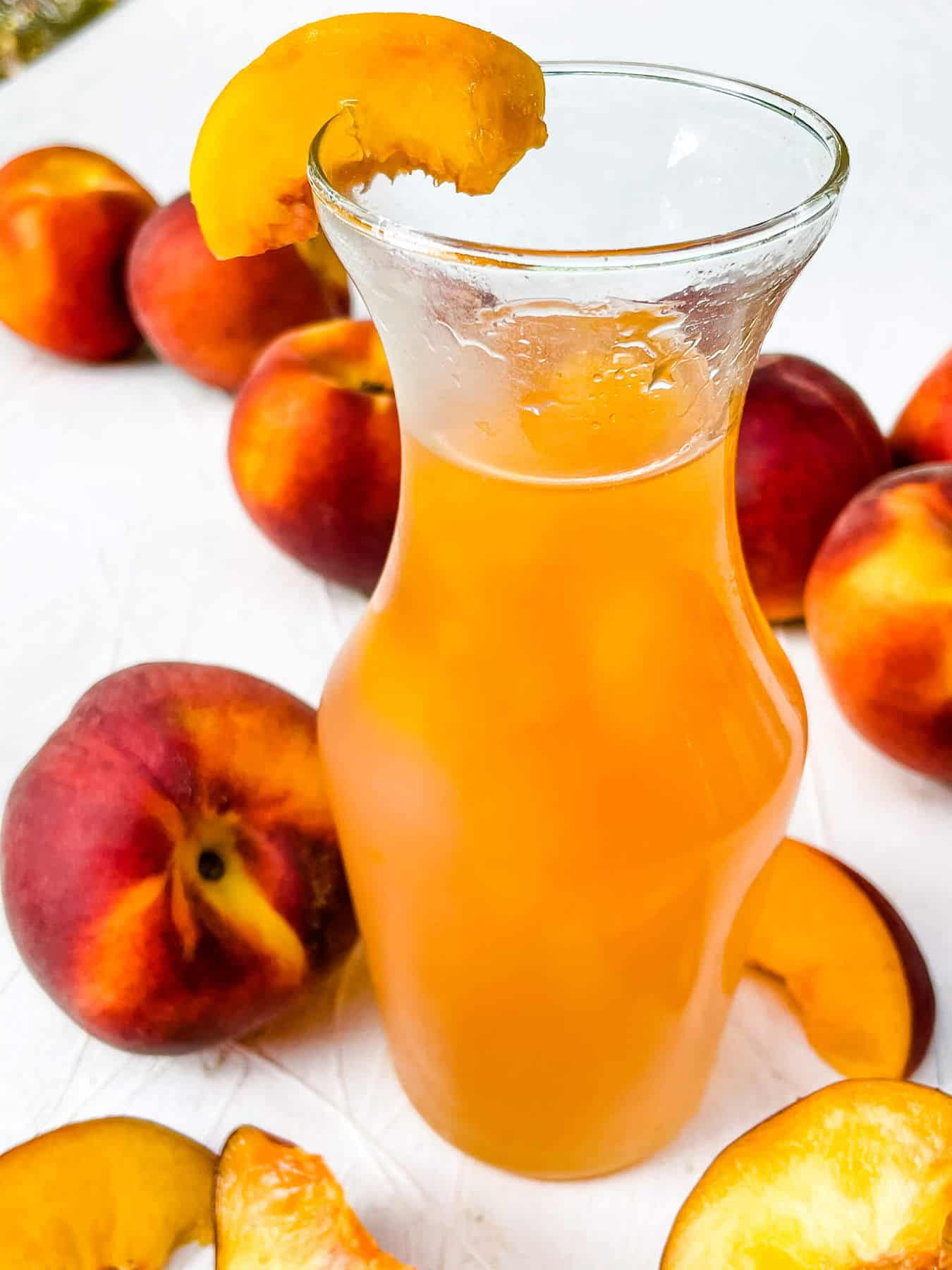 A jar of Peach Syrup with peaches around it