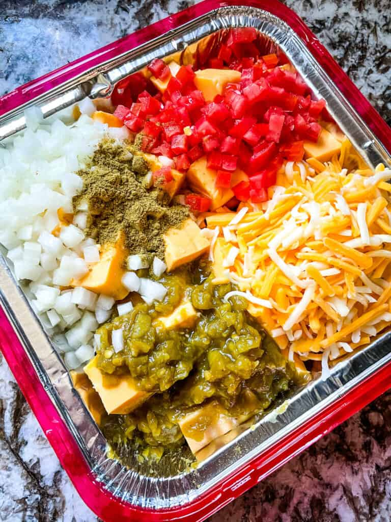 The ingredients for Smoked Queso in a foil pan before cooking