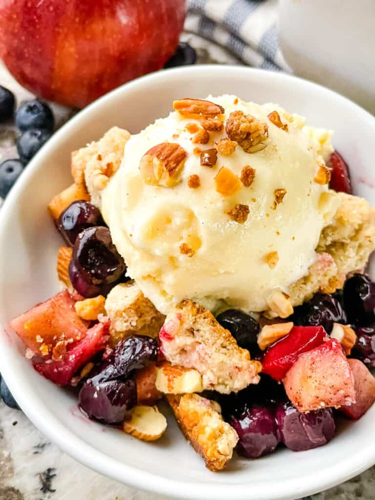 A small white bowl with some crumble and ice cream