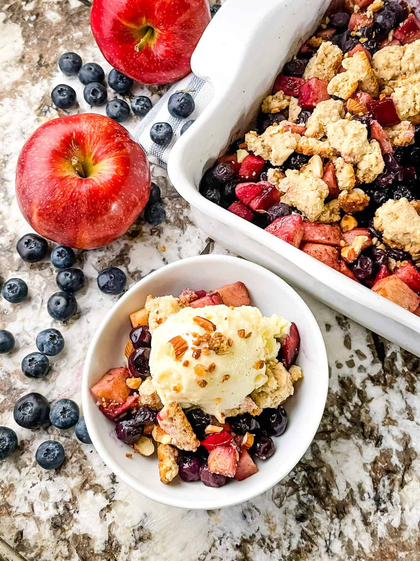 A serving of Apple and Blueberry Crumble in a bowl surrounded by blueberries and the serving dish nearby