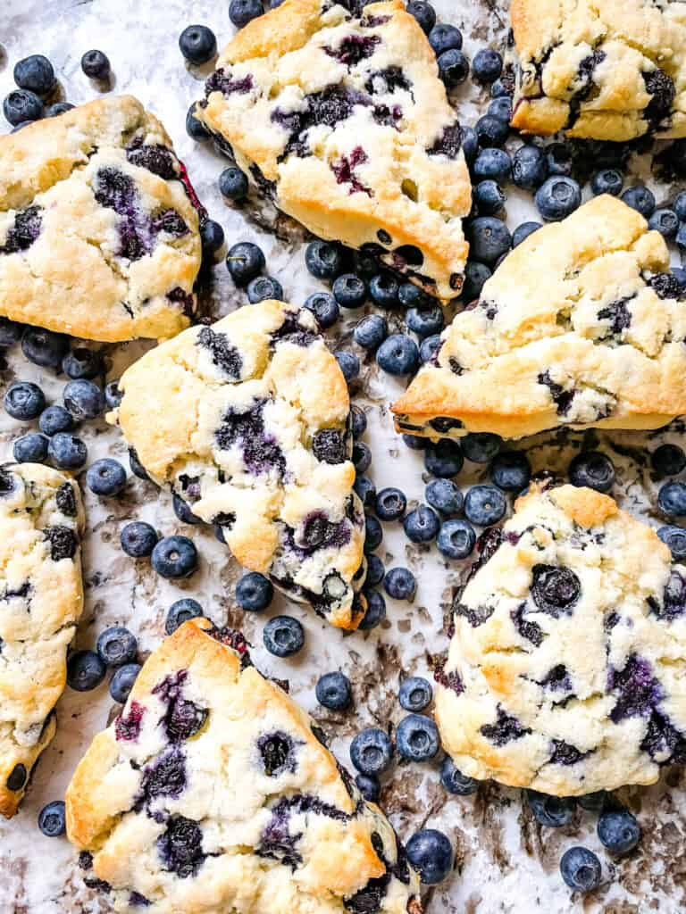 Blueberries Scones scattered on a counter surrounded by blueberries