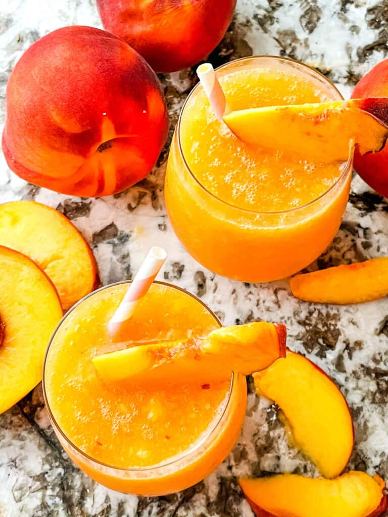 Two peach drinks from the top with peaches around them