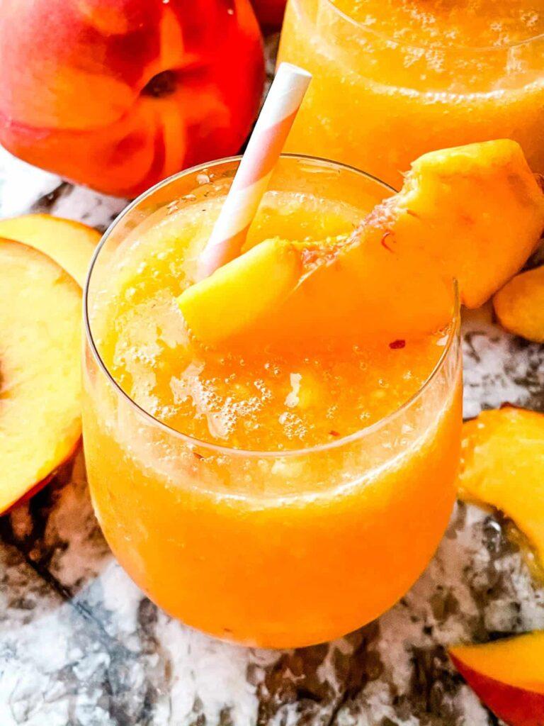 A peach bellini with peaches around it
