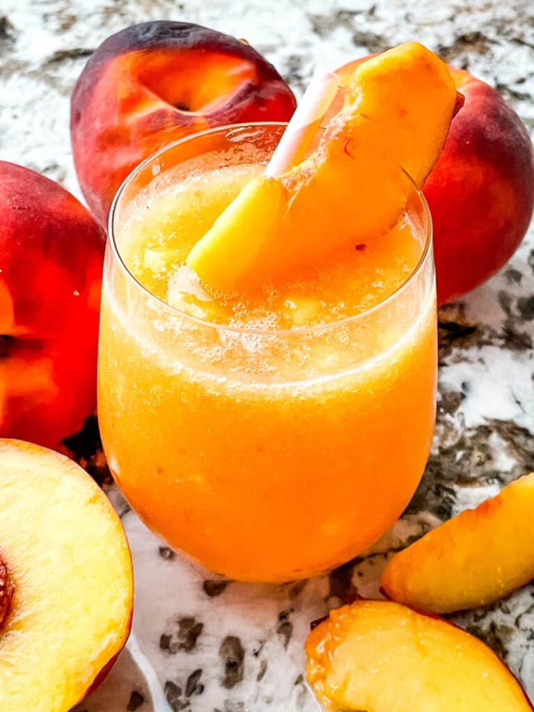 A glass full of the peach drink surrounded by fruit