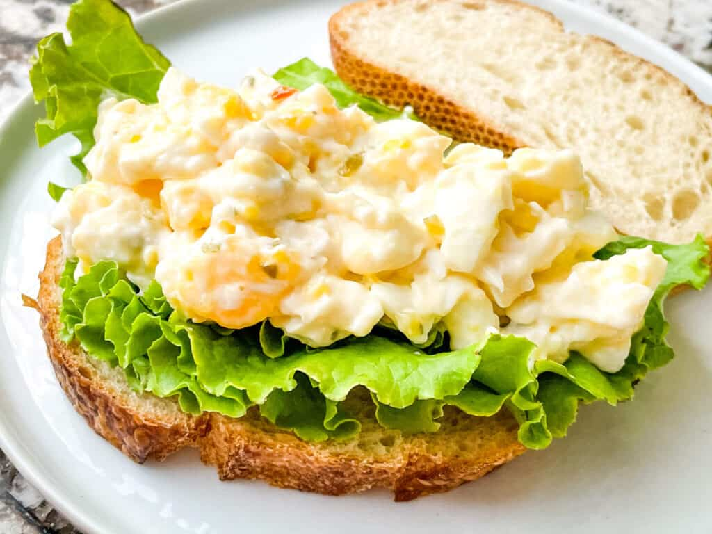 An Egg Salad Sandwich without the top bread piece on a white plate