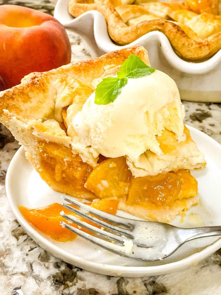Slice of Peach pie with ice cream and a fork