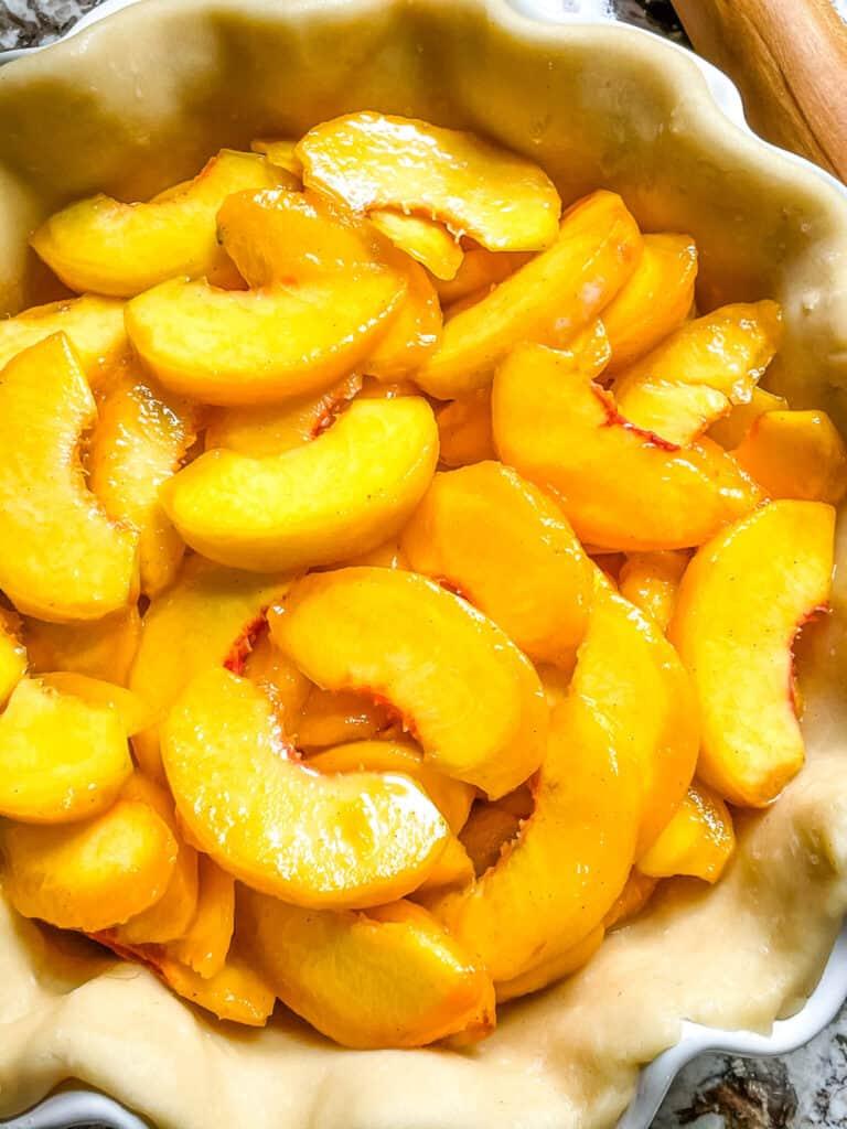 Close up of peach pie filling in the crust
