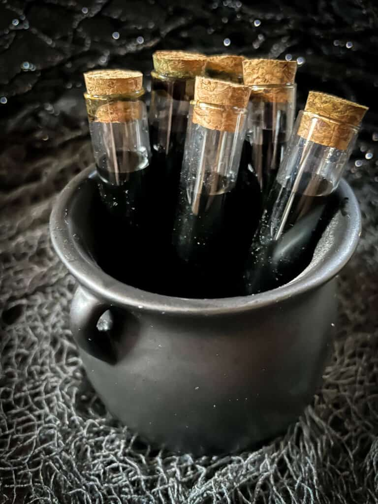 A small black cauldron filled with the poison vials
