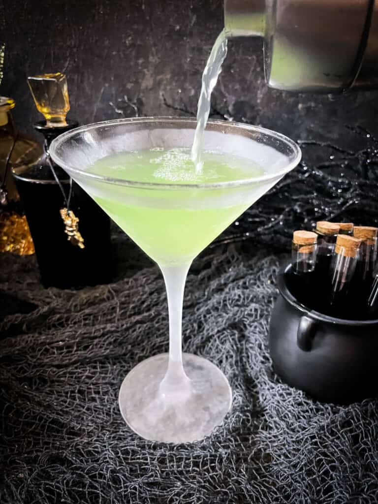 Pouring the green apple mixture into a martini glass