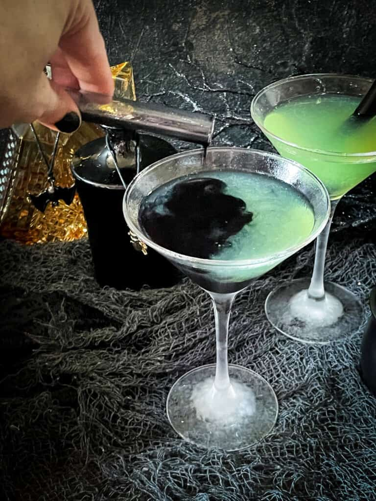 A hand pouring the black poison into a green cocktail