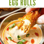 Pin image of a hand dunking a Buffalo Chicken Egg Roll with title at top