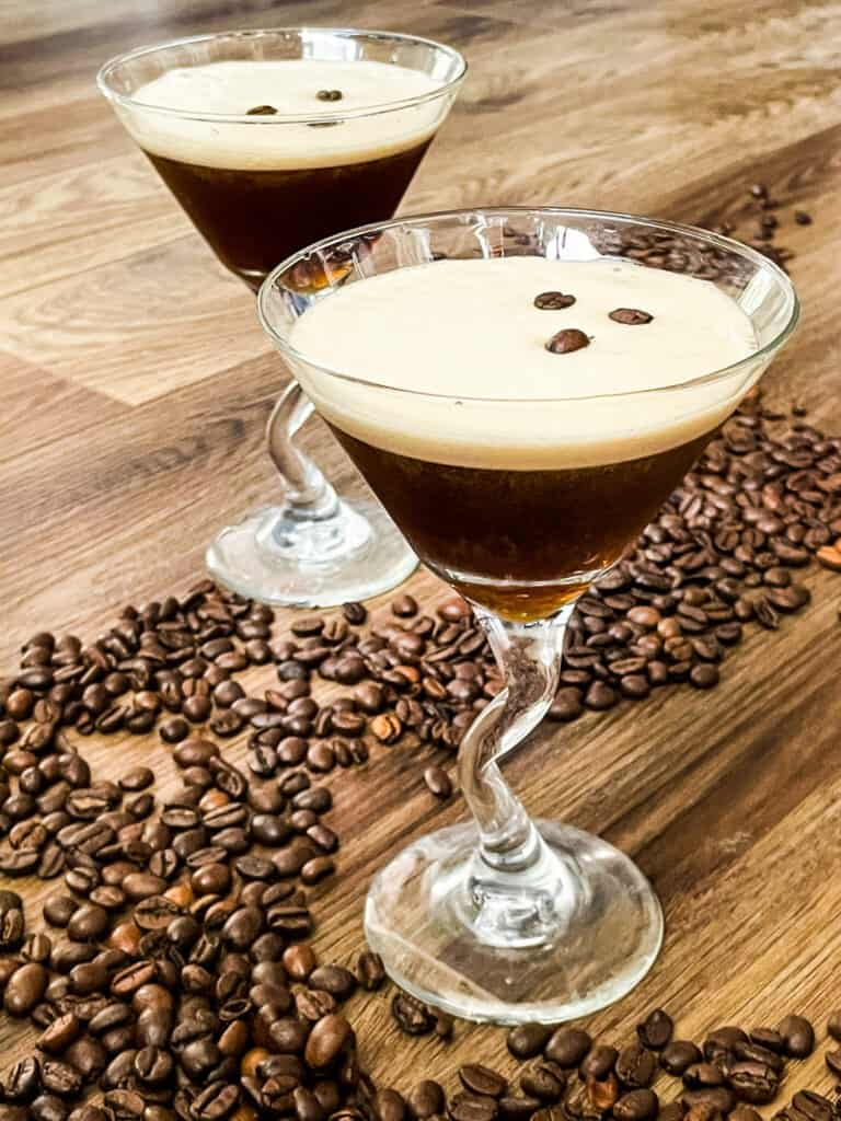 Two full Espresso Martinis with beans around them