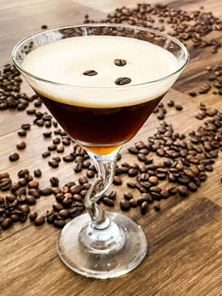 An Espresso Martini in a glass with coffee beans around it