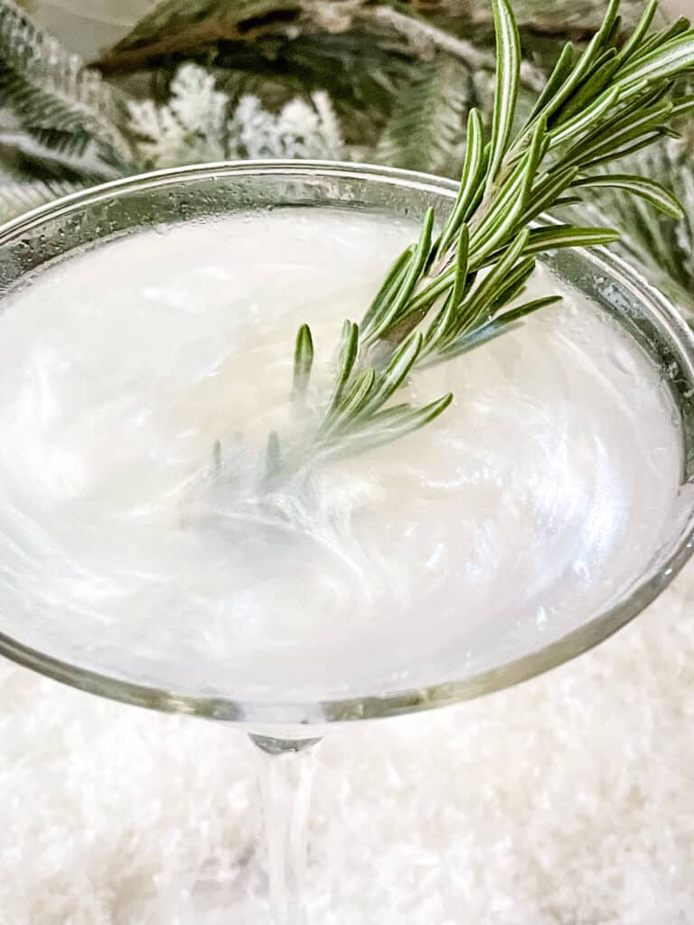 Top view of the swirly white drink with rosemary in it