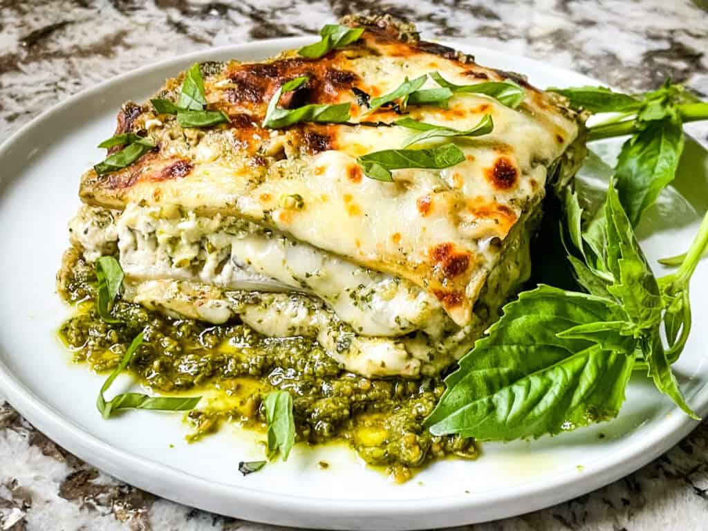 A slice of Lasagna al Pesto on a white plate with fresh basil