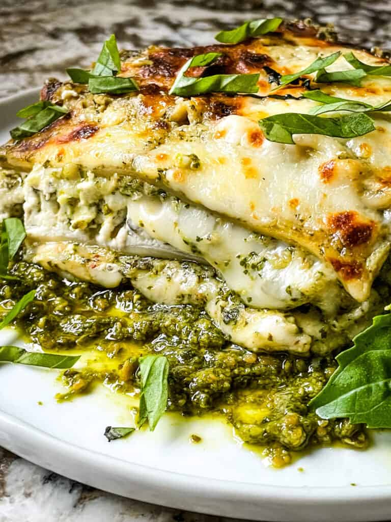 Side view of a slice of Lasagna al Pesto on a white plate