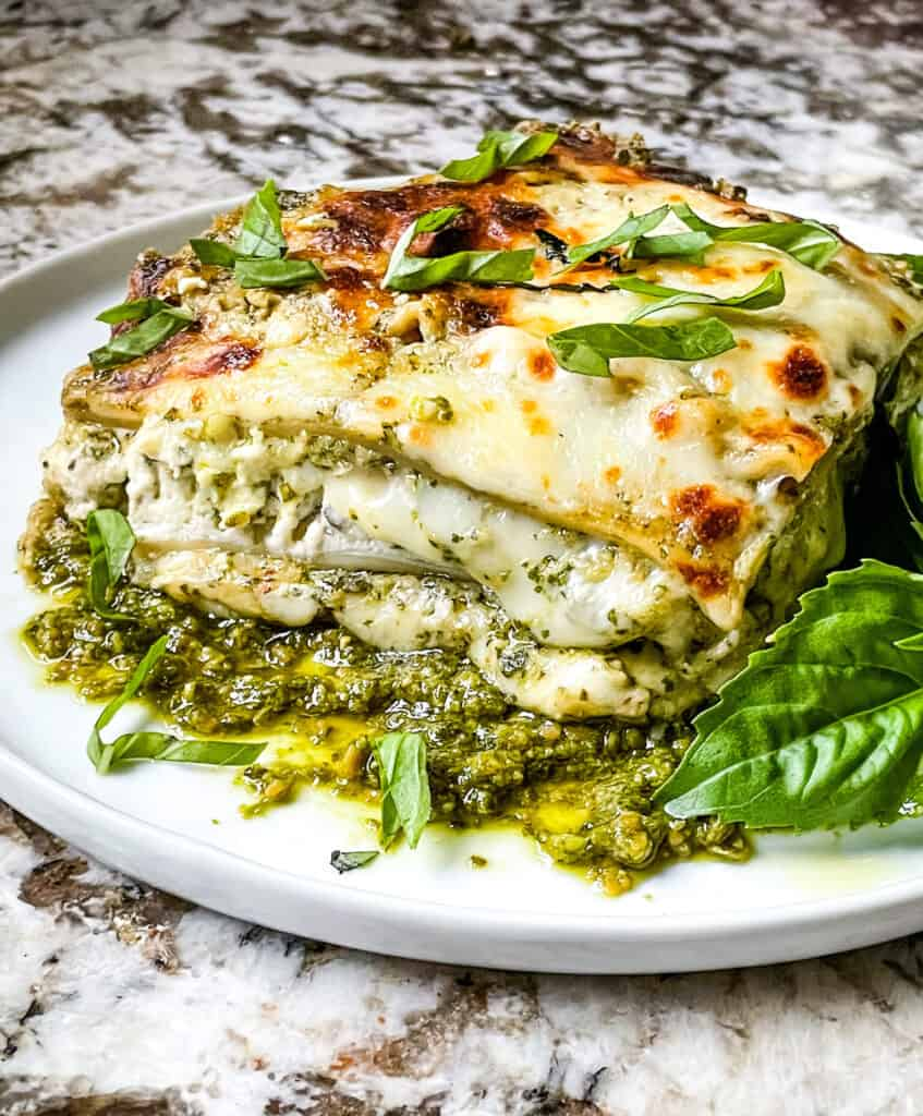 Side view of Lasagna al Pesto on a plate with dresh basil
