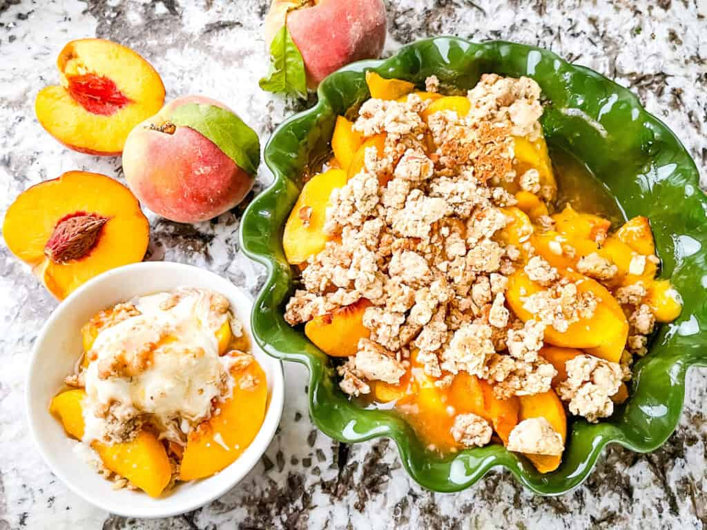 Top view of the Peach Crumble in a green pie dish with a small portion in a white bowl next to it. Peaches around the dishes.
