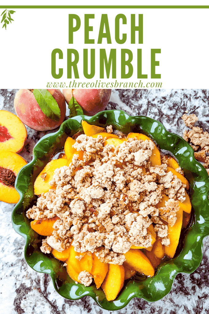Pin image of top view of Peach Crumble in a green dish with peaches around it and title at top