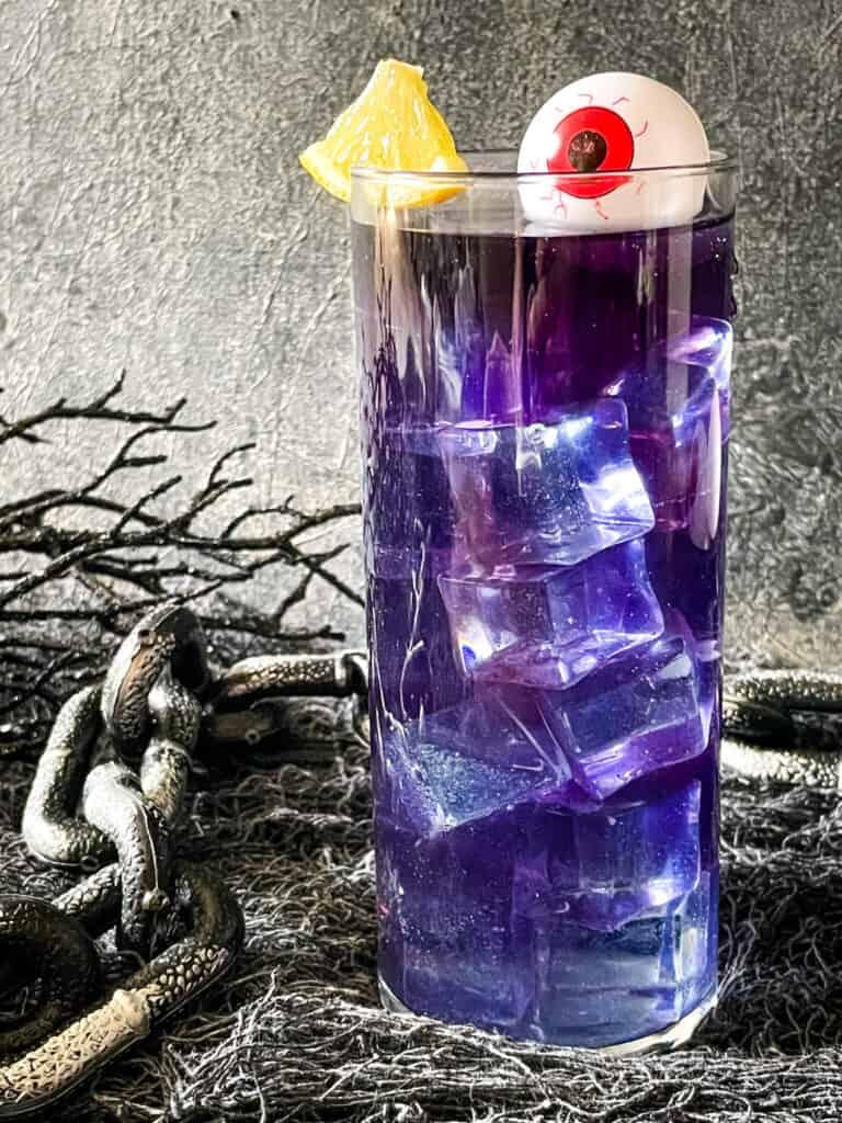 A tall Purple People Eater Halloween Cocktail (+Mocktail)