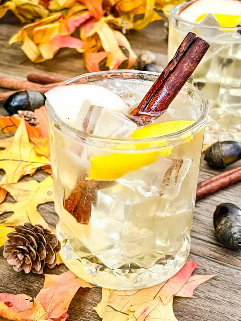 A glass of Whiskey Cider Sour with cinnamon stick and lemon peel