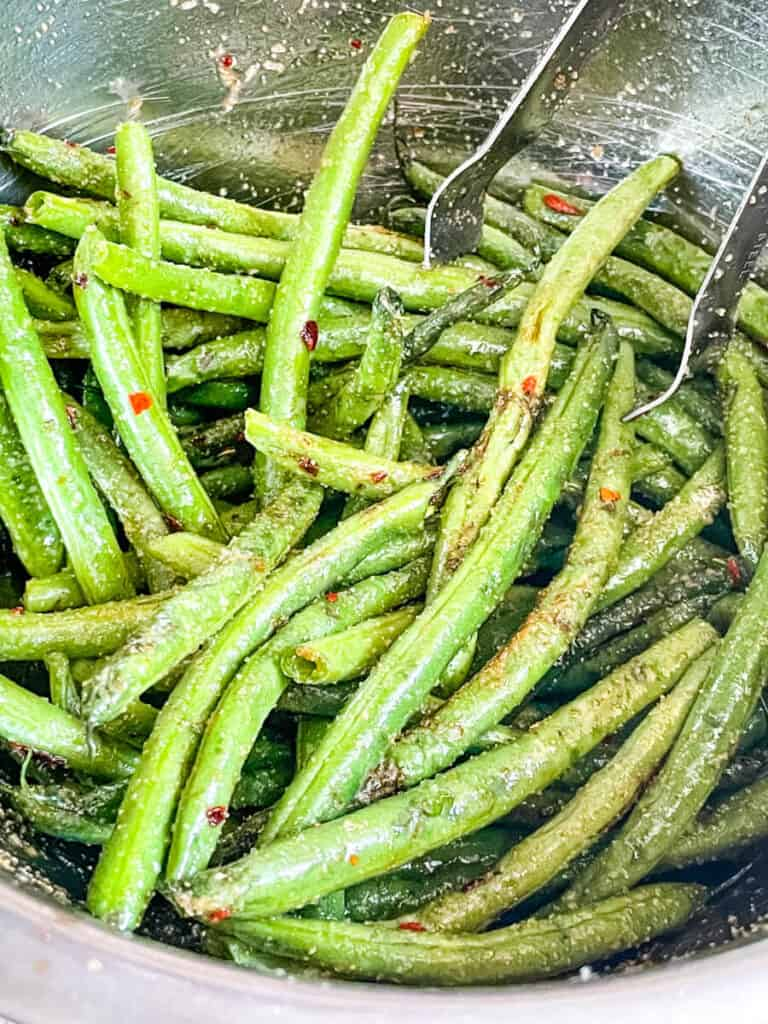 Spicy Asian Air Fryer Green Beans being tossed before cooking