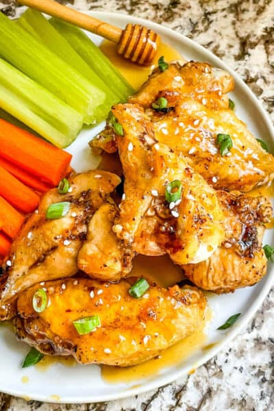 Top view of Honey Garlic Chicken Wings in a pile on a plate with carrots and celery
