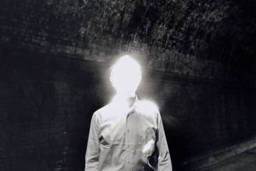 A man in a white coat with an overexposed face that appears completely featurless