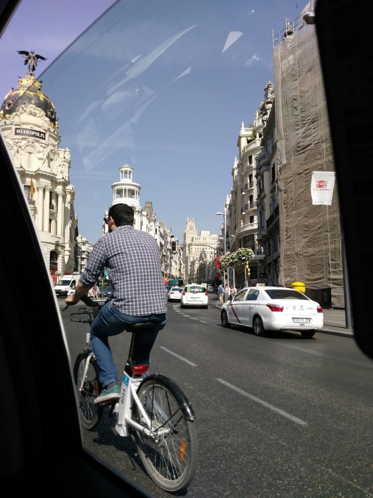 a man on a bicycle through a car window with some pretty buildings in the background