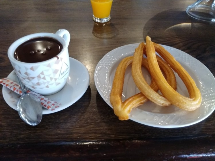 A plate of churros with a cup of chocolate.