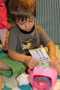 little blonde toddler trying to put a money card into a pink piggy bank