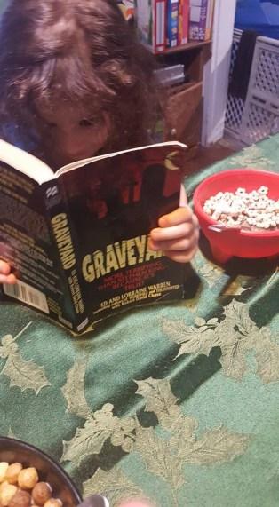 brown hair toddler reading a book
