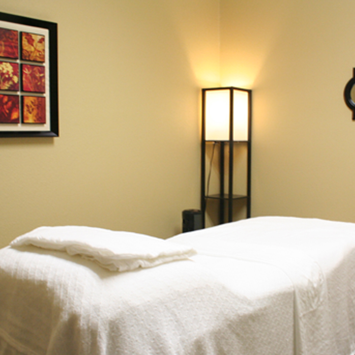Massage bed at Thrive Milpitas with a comfortable massage bed, pillows, decorations including lighting and pictures on the wall.