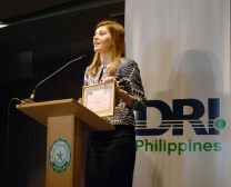 DRI Executive Director Chloe Demrovsky presents a certificate to Ramil Cabodil for DRI Philippines