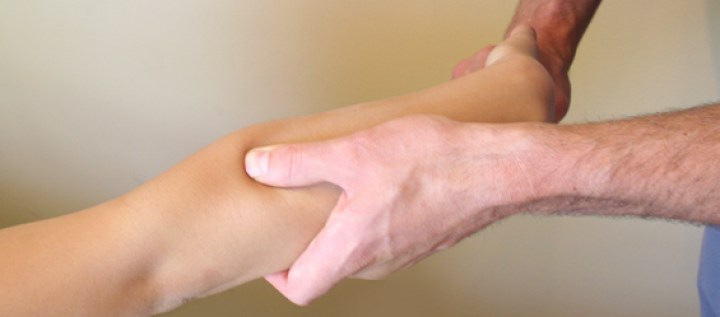 A doctor performing active release therapy techniques on a patient's arm.