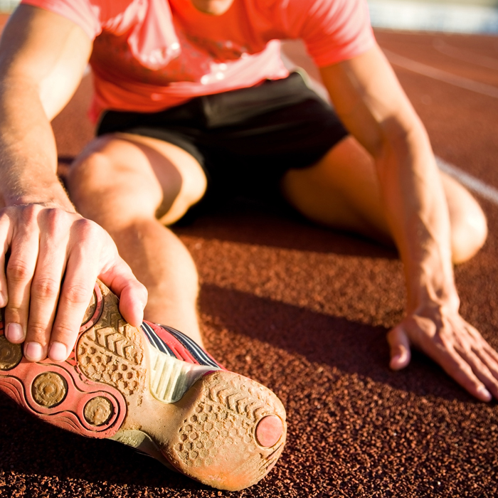 A runner stretching their legs on a track.
