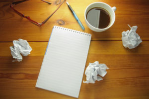 Blank notepad with copyspace surrounded by scrunched up pieces of paper symbolising writers block or brainstorming new ideas