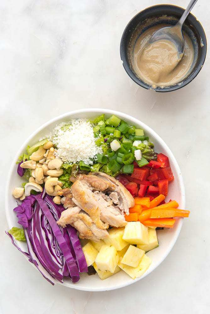 Colorful Asian salad on a plate with a side bowl of dressing
