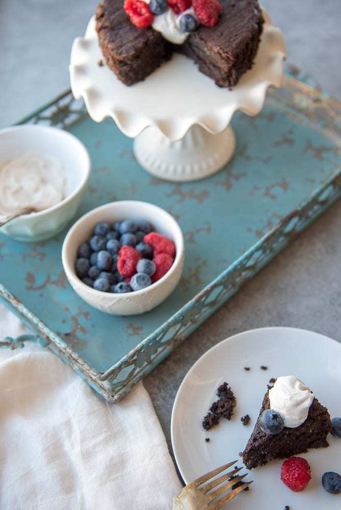 A scene of a chocolate cake on a white stand with fresh berries and coconut whipped cream on a turquoise tray