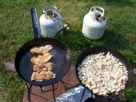 a photo of an outdoor cooking stove and lumberjack frying pans with walleye and potatoes cooking at silsby lake lodge manitoba canada