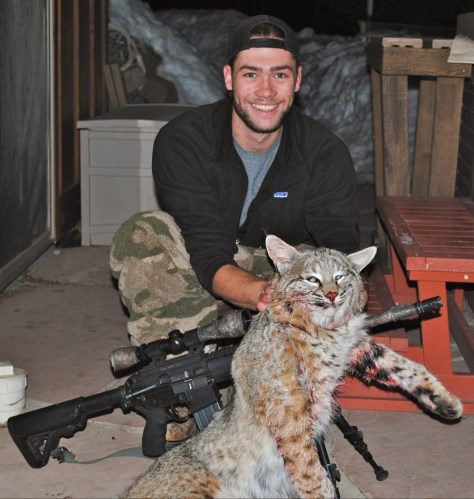 A Young Hunter Poses with a Big Male Bobcat Taken with an AR-15 while Predator Hunting at Night in Northwestern Colorado