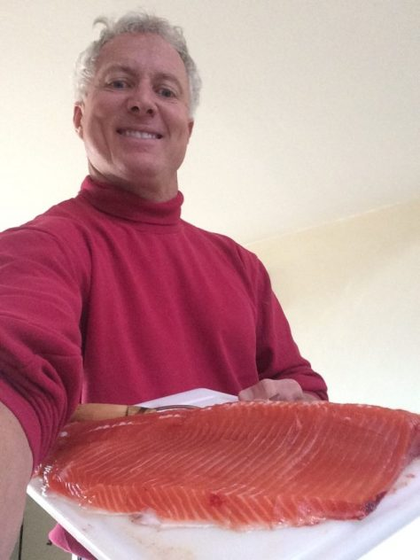 A fisherman poses with a fillet of a big trophy rainbow trout, before brining for the smoker