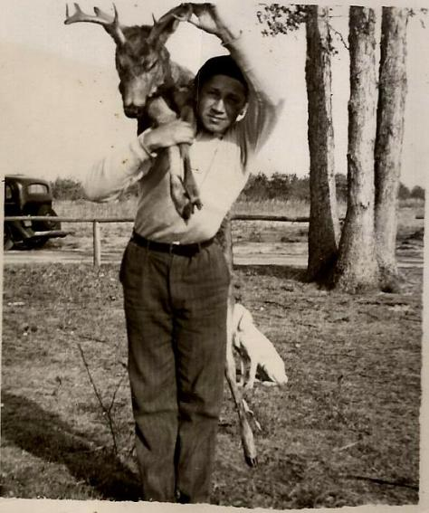 A vintage hunting photograph of a Teen-Aged Boy Carrying a Buck White-tailed Deer Over His Shoulder Which He Harvested With a Shotgun in the Late 1930's in Southern New Jersey. The deer hunter is Mark A. McCarty Sr. From The Collection of Michael Patrick McCarty