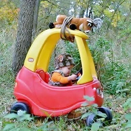 A Future Young Hunter Drives His Toy Car Through The Woods, With a Stuffed Deer Toy On Top of the Roof. Teach A Child to Hunt - Today!