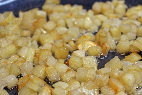 Diced potatoes frying in a skillet.