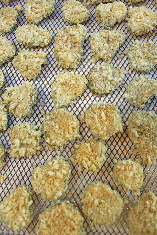 Breaded pickles on the air fryer basket ready to be air fried.